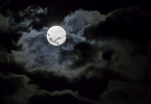 Sognare la luna piena che appare di notte; la sua luce si affaccia tra le nubi
